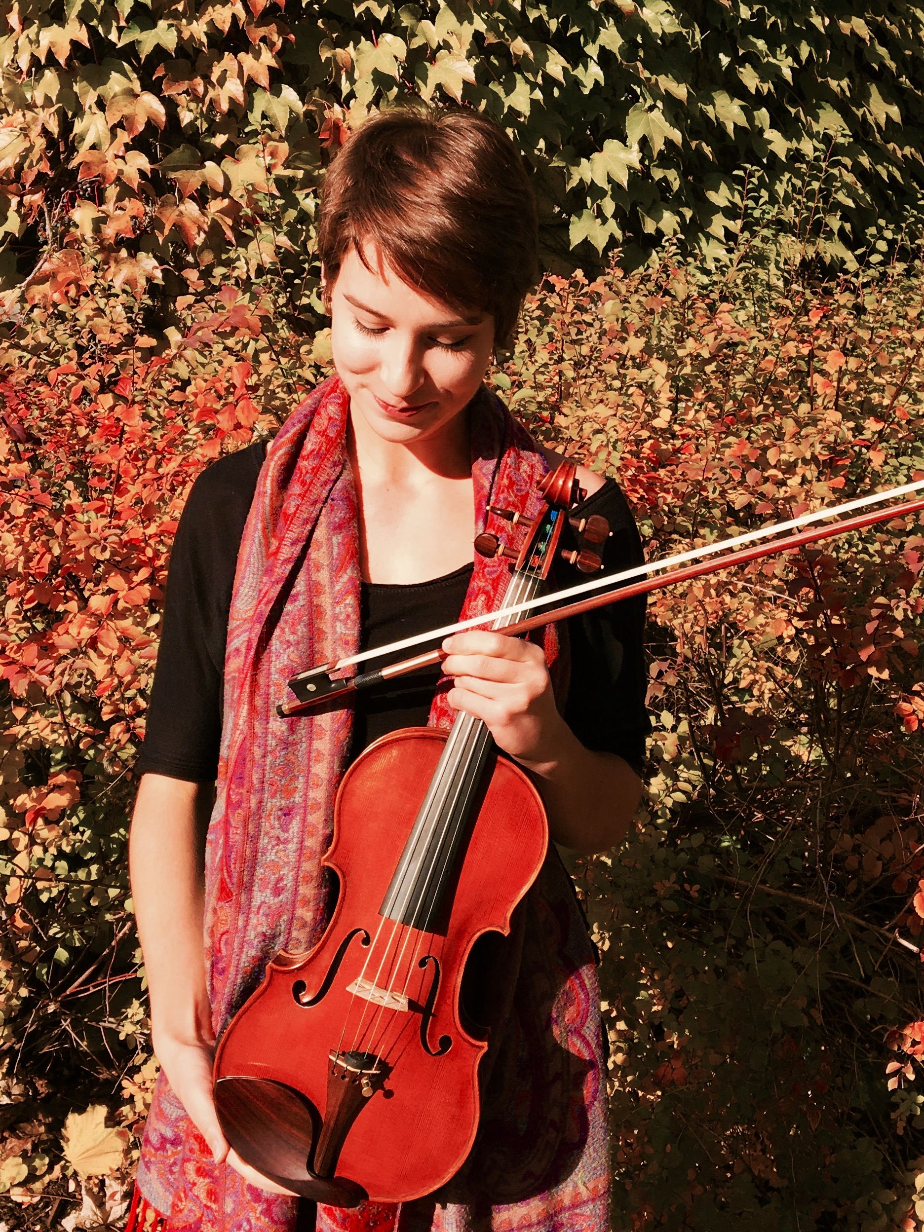Photo of Isabelle Lebeuf-Taylor with violin, fall foliage in background