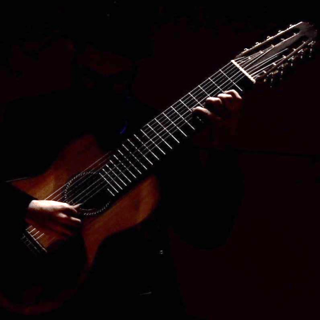Photo of six-string guitar with hand strumming strings