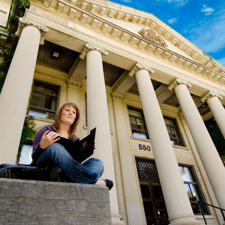A pensive student in front of Tabaret Hall